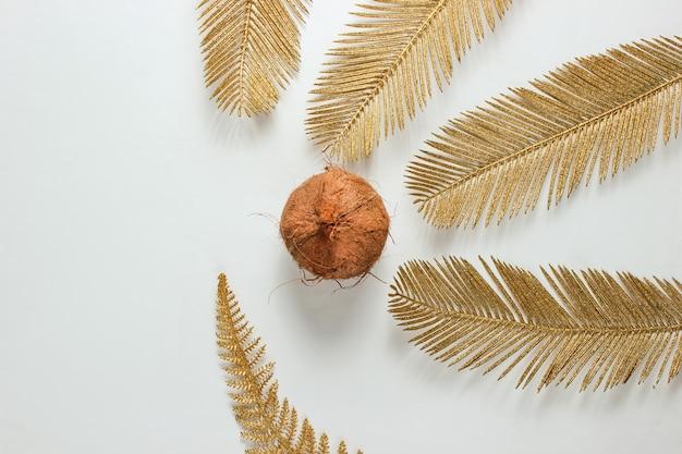 ミニマルなトロピカルな静物。白い背景に金色のヤシの葉とココナッツ。ファッションコンセプト。上面図。