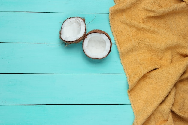 Minimalistic tropical vacation concept. coconut halves, towel on a blue wooden background. top view