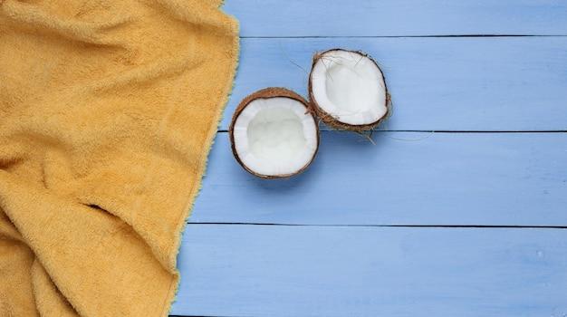 Минималистичная концепция тропического отдыха. половинки кокоса, полотенце на синем деревянном