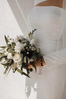 Minimalistic wedding dress for the bride and beautiful wedding bouquet made of white flowers and greenery, classy attire