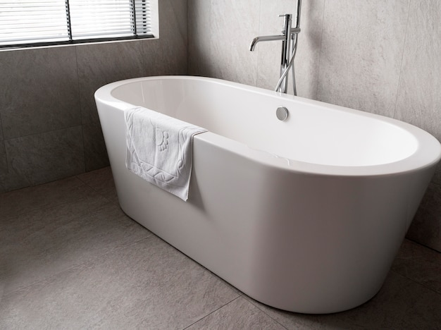 Минималистичная белая ванна с полотенцем на ней