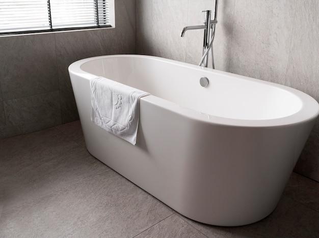 Minimalistic white bathtub with a towel on it