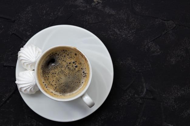 黒いテーブル、上面にコーヒーのミニマルな白いカップ。