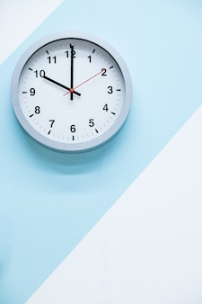 Minimalistic white wall clock with light metal on a blue white background. time concept.