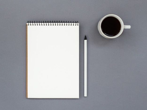Minimalistic workplace with white blank paper notebook mockup and cup of black coffee on gray. top view.