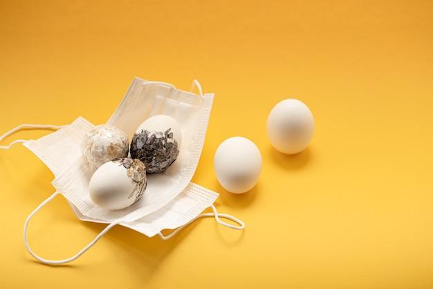 Le uova di pasqua decorate minimamente sono mascherate contro il coronavirus. pasqua celebrazione sicura concetto.