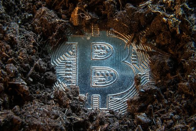 마이닝 암호화 통화-비트 코인, 흙 땅에있는 디지털 화폐 동전.