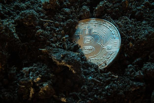 마이닝 암호화 통화-bitcoin, 흙 바닥에있는 온라인 돈 동전.