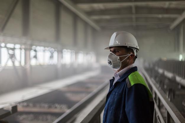 白いヘルメットと防毒マスクの鉱山技術者がほこりの多い汚れたワークショップを検査します。
