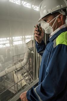 Горный инженер в респираторе в белом шлеме контролирует работу гранитной мастерской