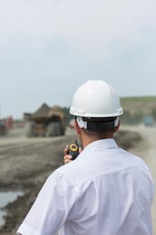 Горный инженер в белой рубашке и шлеме контролирует вождение самосвалов в карьере
