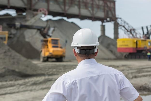 白いシャツとヘルメットの鉱山エンジニアが花崗岩のワークショップの作業を監督