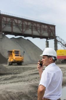 Mining engineer supervises work of granite workshop holding walkie-talkie