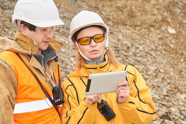 Горные инженеры обсуждают рабочую документацию на открытом воздухе на горном участке