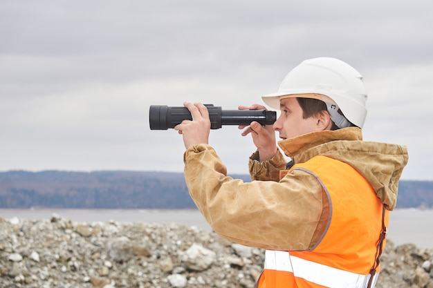 Горный или дорожный инженер, использующий зрительную трубу на фоне карьера на берегу реки