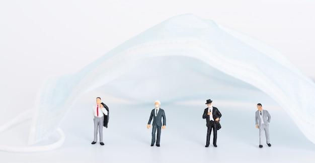 パンデミックコロナウイルス(covid-19)の摩耗のマスクのため、ミニチュアビジネスの人々は白い背景の上の外科のマスの下で社会的な距離をとります。