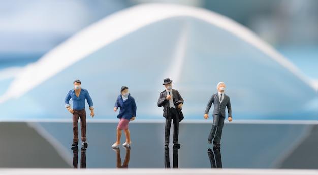 ミニチュアビジネス人々は青い背景に携帯電話でマスクスタンドを着用します。