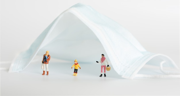 ミニチュア家族の人々はパンデミックコロナウイルス(covid-19)の摩耗マスクが概念的な生命を救うことができるため、白い背景の上の外科マスの下で社会的距離を置きます。