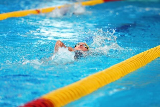 ミンスク、ベラルーシ-2019年8月20日:きれいな水でプールで若い水泳選手の列車