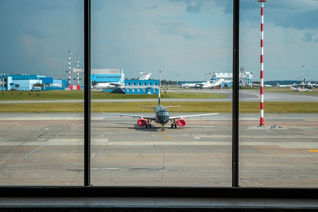 Minsk, belarus - june 16, 2021 minsk international airport. the view from the window dwindled to the runway and airplanes. international passenger transportation.