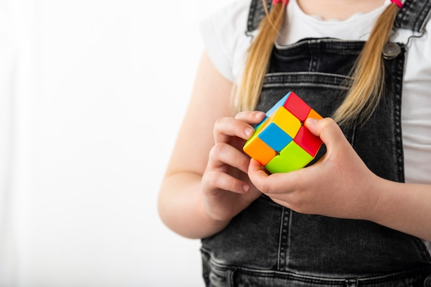 Minsk, belarus, june 9, 2020: rubik's cube in the hands of a little girl. a child holds a rubik's cube on a light background, playing with it