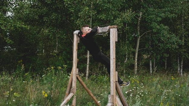 ミンスクブララス。 2019年7月28日晴れた日。ブーツやスポーツ競技の障害物コース中にハードルを通過する男