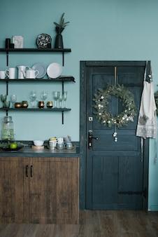 민트 블루 주방 인테리어와 크리스마스 장식. 부엌의 개념에 따라 집에서 저녁 식사를 요리하십시오.