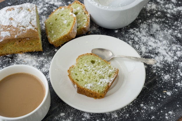 Mint cake sprinkled with powdered sugar on dark surface with cup of coffee