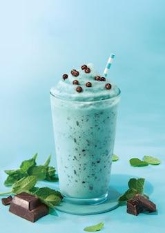 Мятный шоколадный молочный коктейль на бирюзовом цветном фоне