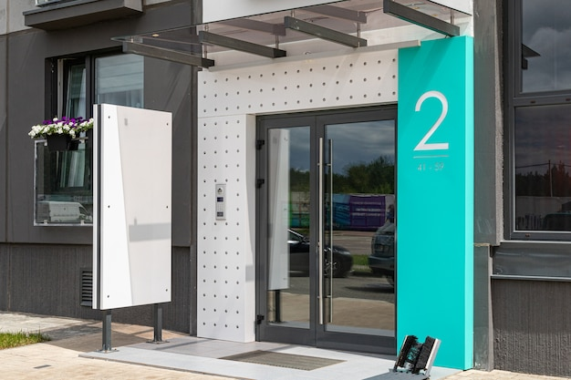 Mint-colored, white and gray entrance to highrise with entryphone and blank tablet