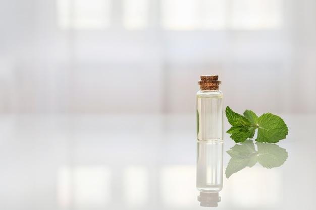 ガラステーブルの上の小さなボトルにエッセンシャルオイルをミントします。