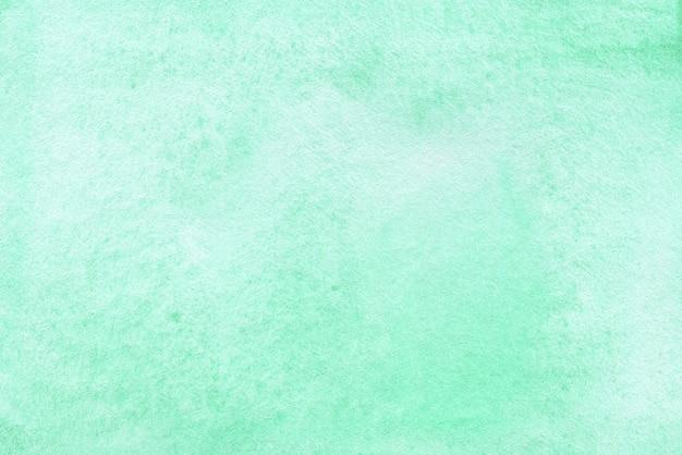 織り目加工の紙にミントグリーンの抽象的な水彩画の背景