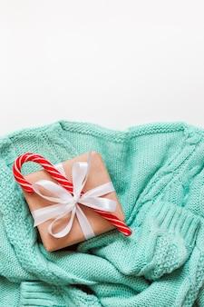 白い背景に飾られたギフトゼロ廃棄物とミントグリーンの居心地の良いセーター。休日のコンセプト。