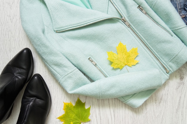 Mint jacket, black shoes and maple leaves. fashionable concept