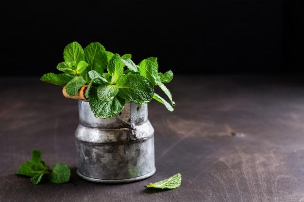 ミントの葉、古い暗闇の古い素朴なバケツの花瓶にミントの新鮮な花束。