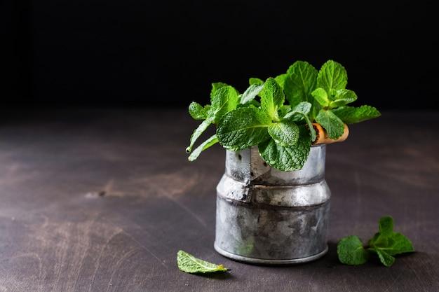 ミントの葉、古い素朴なバケツの花瓶にミントの新鮮な花束