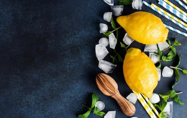 ミントの葉、新鮮なレモンと蜂蜜は、青いコンクリートのテーブルにメッシュのショッピングコットンバッグを持って横たわっています。上面図。ゼロウェイストコンセプト。