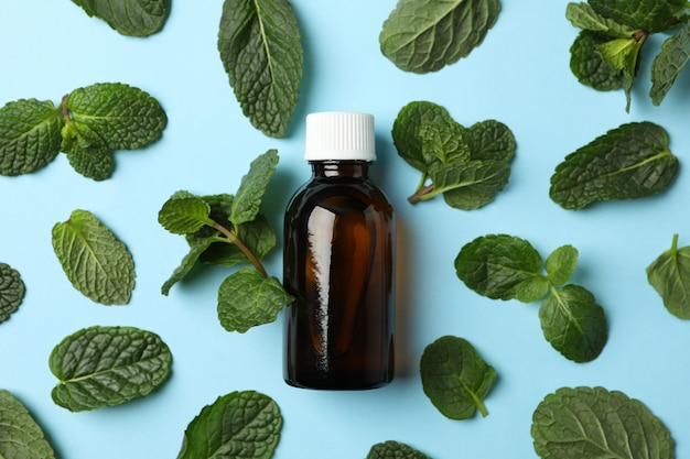 Mint leaves and medical bottle on blue, top view