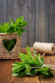 Листья мяты на деревянных фоне. летние напитки или десертный ингредиент. деревенский стиль