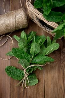 Листья мяты на деревянных фоне. летние напитки или десертный ингредиент.