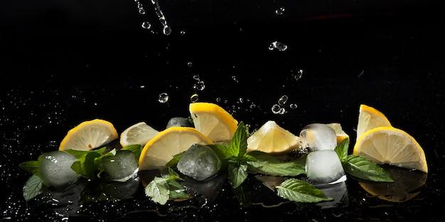 暗い背景に水のしぶきのミント、レモン、氷
