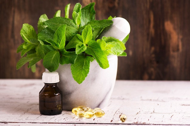 Mint sprigs, peppermint oil and pills over wooden table
