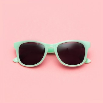 Mint sunglasses isolated on pink background.