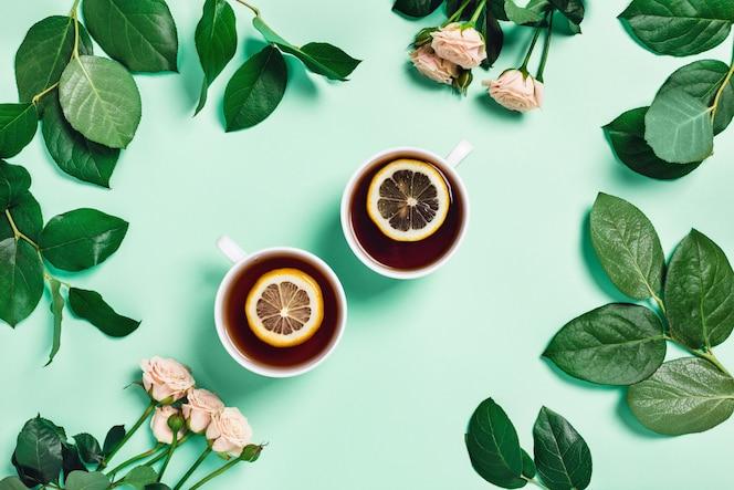 Мятный стол с двумя чашками чая и цветов.