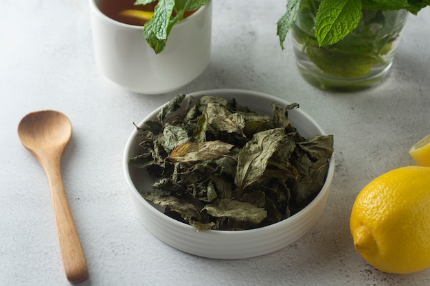 Mint tea, dry mint leaves in bow, over light surface, isolated,