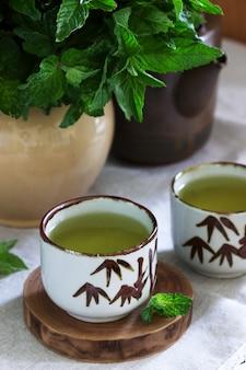 Мятный чай в винтажном китайском чайном наборе и мятный букет в кувшине