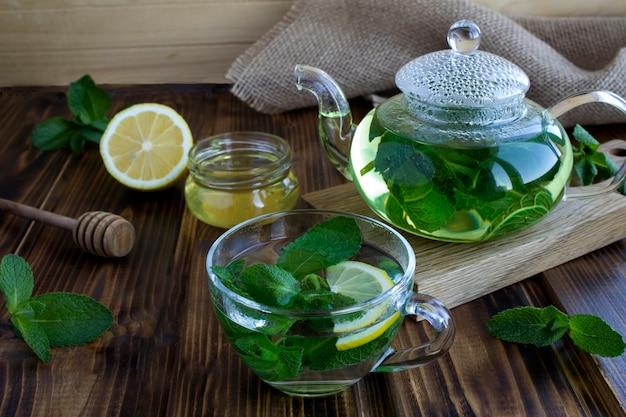 ガラスのカップにミントティー、素朴な木製のテーブルにティーポット。健康的な飲み物。閉じる。