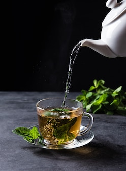 Mint tea pours from the teapot into a clear ã'âup on black background