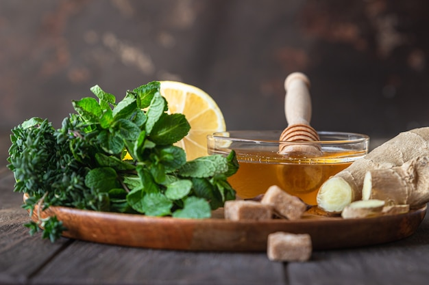 Mint, thyme, ginger root, lemon, honey and brown sugar. ingredients for making ginger or herbal tea.