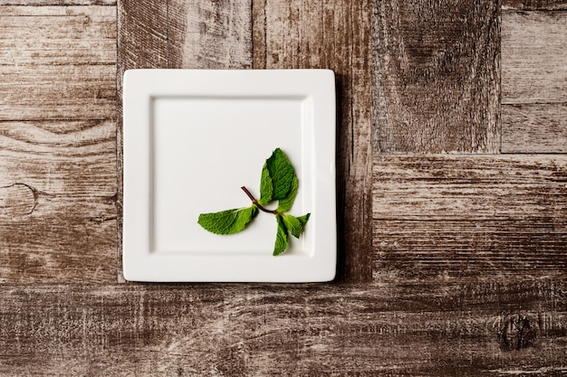 Mint on white plate on wooden